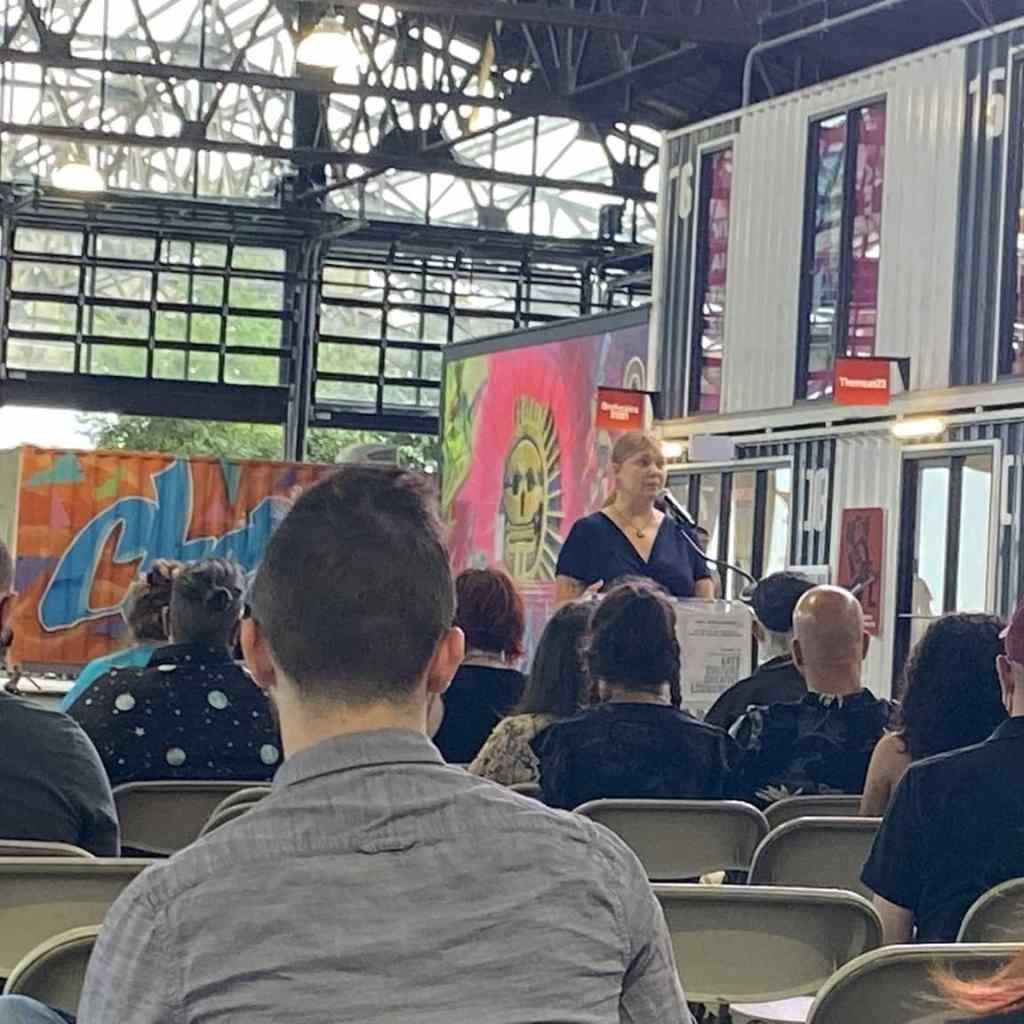 The blog author is wearing a blue dress and reading at a podium in front of a crowd in a high-ceilinged industrial space.